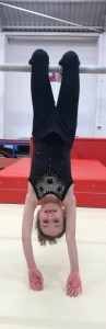 Young girl gymnasts dangles upside down at Tumbles Academy of Gymnastics in Lowton