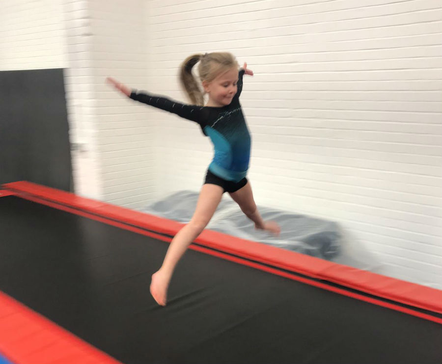 Young girl jumps on trampoline at Tumbles Academy of Gymnastics in Lowton