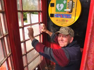 Brian Thilwind helps repair the former red telephone box on Slag Lane, now used as a defibrillator cabinet.