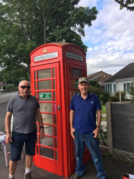 Stan Crook and Brian Thilwind with the newly repaired and repainted phone box on Slag Lane that is now a defibrillator.