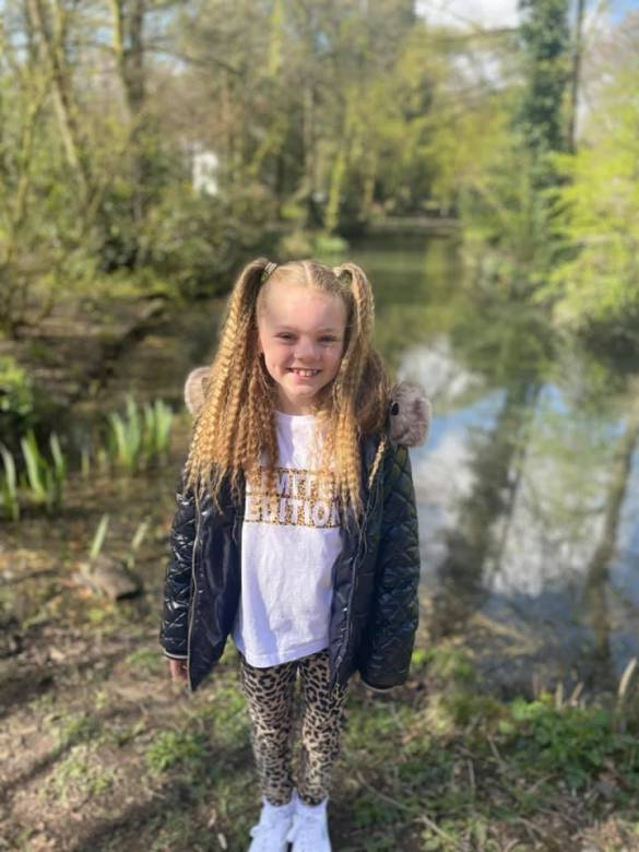 Young girl stands by pond