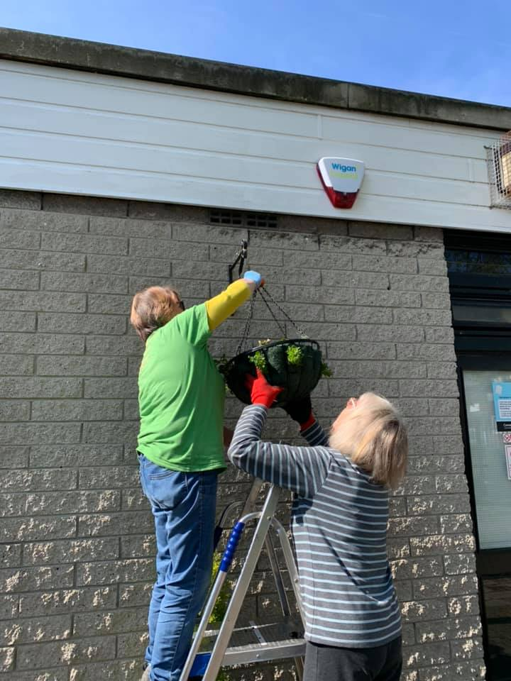 Golborne in Bloom volunteers put up hanging baskets at the library