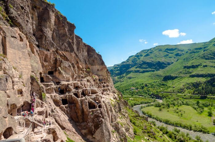 The side of a red mountain dotted with caves overlooking a green valley with a river flowing through it.