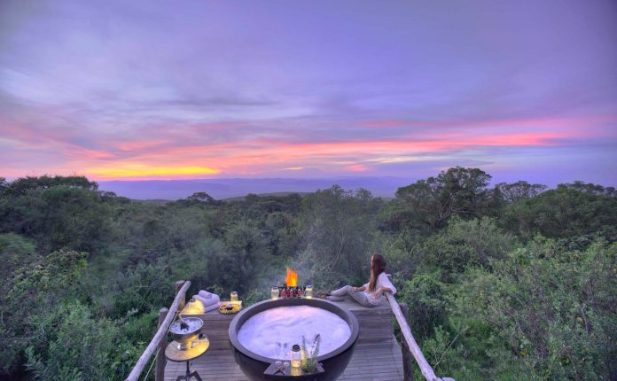 A woman reclines on a wooden deck and looks out on the wilderness from a wooden deck at sundown. The deck has a hot tub, candles and small tables.
