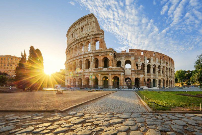 Guardando su ruvidi ciottoli verso un sole splendente che alza sopra alcuni alberi distanti, il Colosseo si erge a destra in una luce dorata sotto un cielo blu con nuvole simili a cotone sopra;  un inizio anticipato aiuta a garantire un fine settimana perfetto a Roma