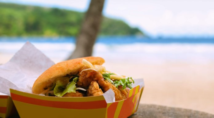 An open cardboard carton containing a flatbread stuffed with pieces of deep-fried shark lettuce and other fillings, is sitting on a table outside. The trunk of a plam tree and the beach and sea beyond, is out of focus in the background