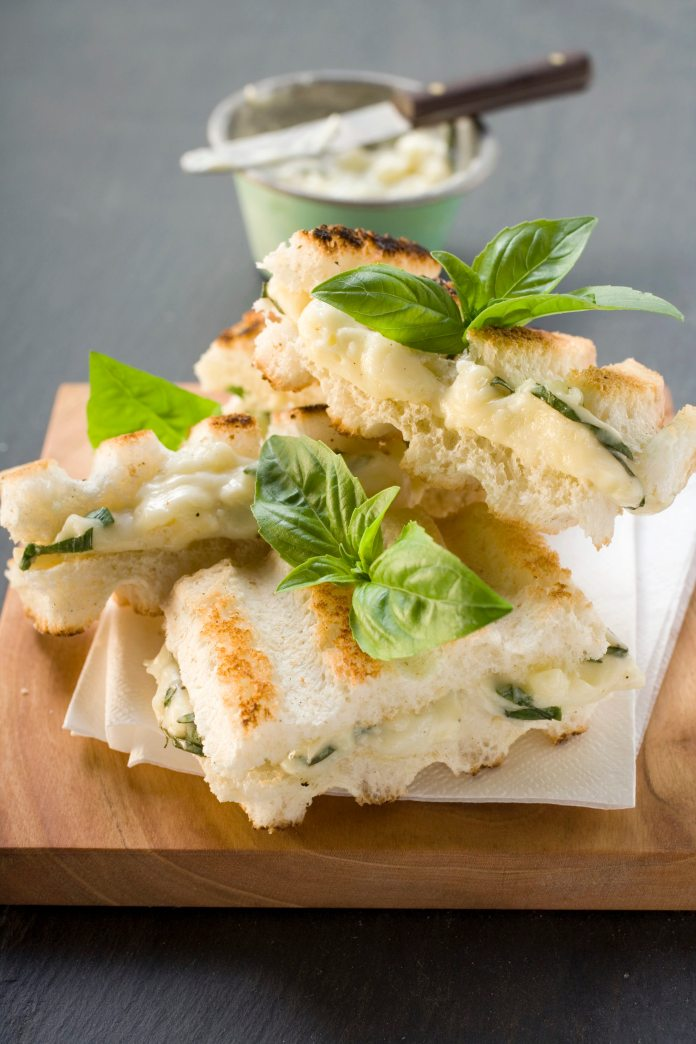 A stack of toasted tramezzini, filled with melted mozzarella and chives, sitting on white paper napkins a wooden chopping board. Sprigs of basil have been artfully placed as decoration.