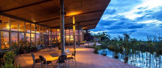 Tavoli e sedie sono disposti intorno al cortile che si affaccia su uno specchio d'acqua ricco di vegetazione;  resort eco lusso