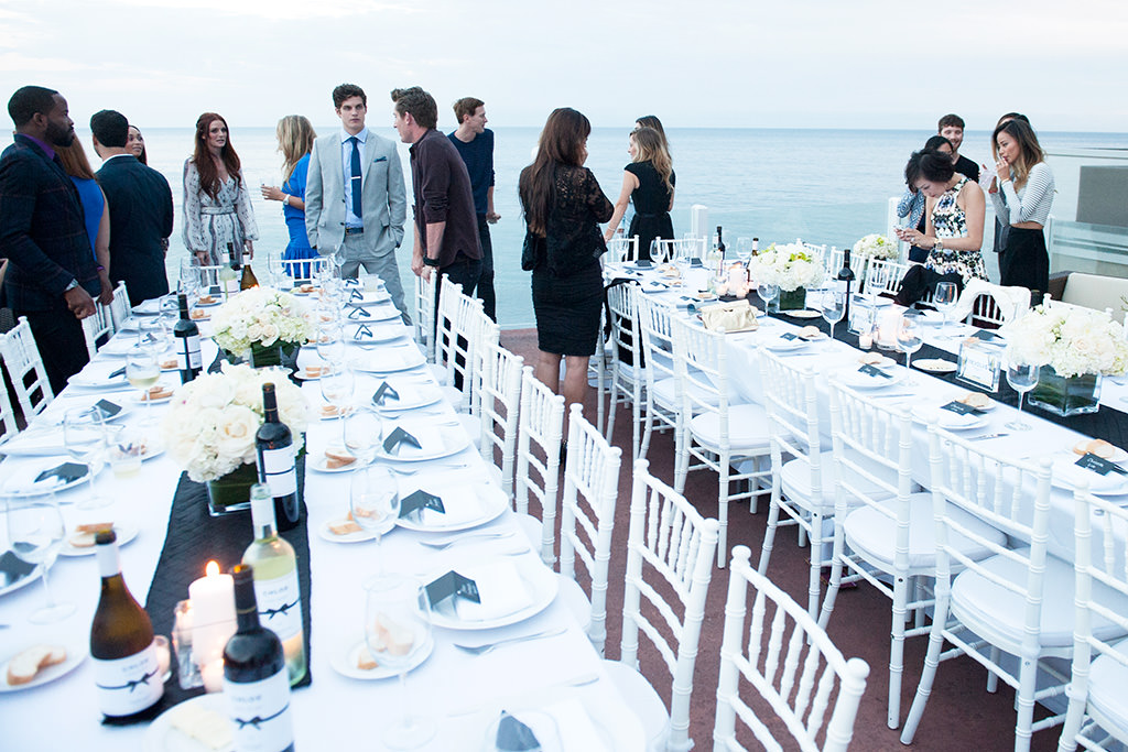 photo of guests at forty-plus person formal dinner on deck of Revolve Malibu Beach House overlooking ocean produced by lob•group