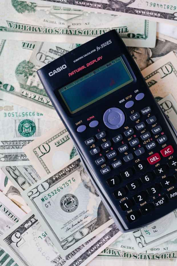 calculator placed over stack of usa dollars