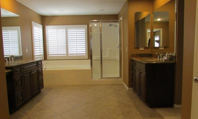 Spacious Master Bath with his and her vanities, soaking tub and