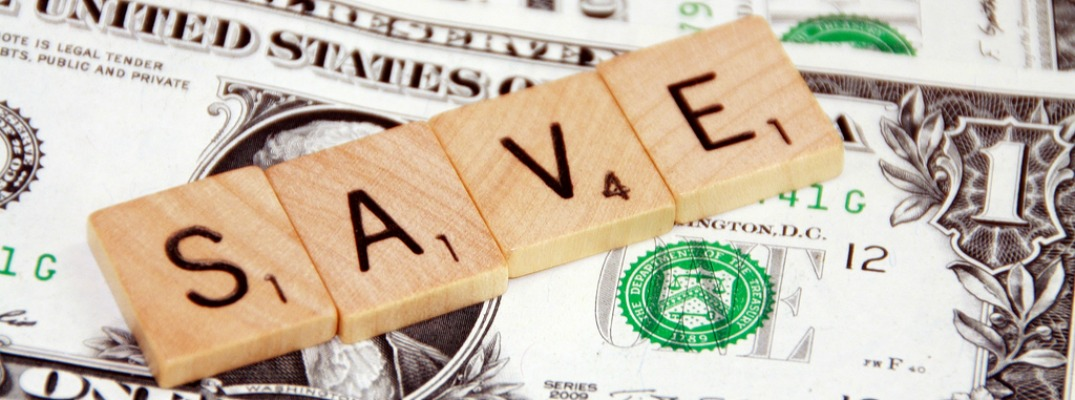 the word save spelled in scrabble tiles sitting on top of american money