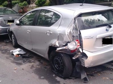 Silver hatchback car with rear end damage implying a hit and run accident