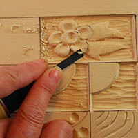 shaping a relief wood carving with a straight chisel