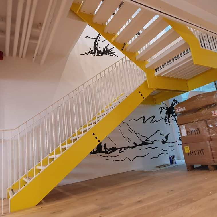 yellow-and-white staircase at WeWork, Merchant St, London, by LSJ Engineering
