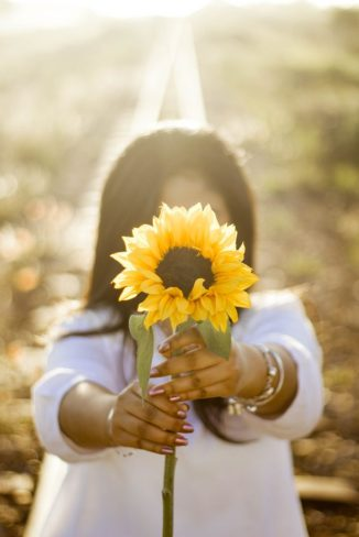 Image of woman holding out a sunflower as an offering of thanks, gratitude, and love.