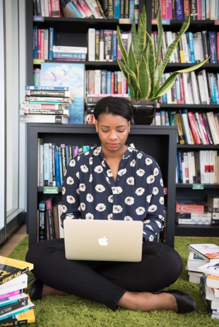 Image of a person in a library, laptop open doing research. This image symbolizes Heather taking her health into her own hands by researching a vulvar specialist to confirm her diagnoses and get her onto treatment.