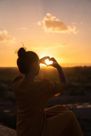 Image of person holding up their hands in the shape of a heart to the sky at sunset, signifying the release of self-blame for my LS..