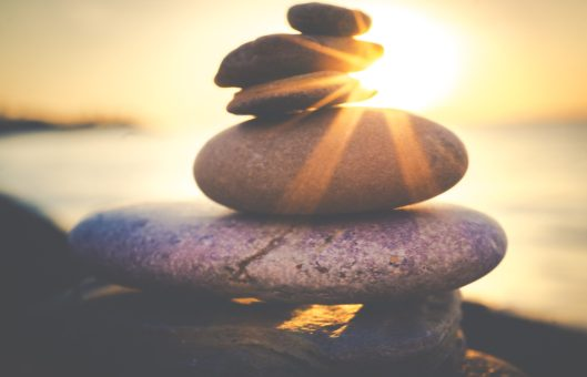 Image of pebbles stacked on top of each other on a beach at sunset. This represents the balance that nutrition therapy seeks to restore to the body.