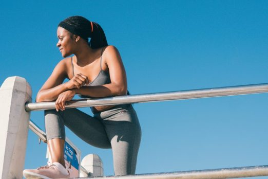 Image of person leaning against a bar in workout gear.