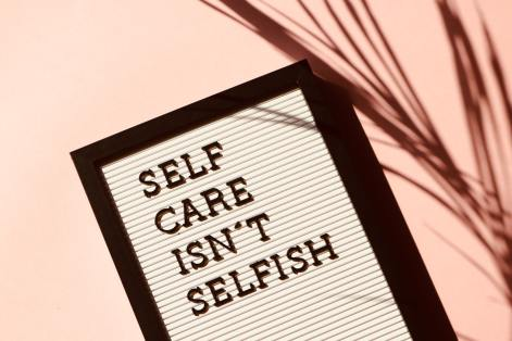 """Image with a sign reading """"Self Care isn't Selfish"""" amongst a pink background next to a plant. This symbolizes the love I showed myself when I listened to my body and took a break from using dilators."""