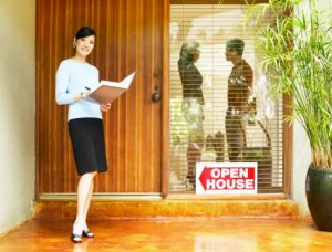 Realtor with documents smiling outside house