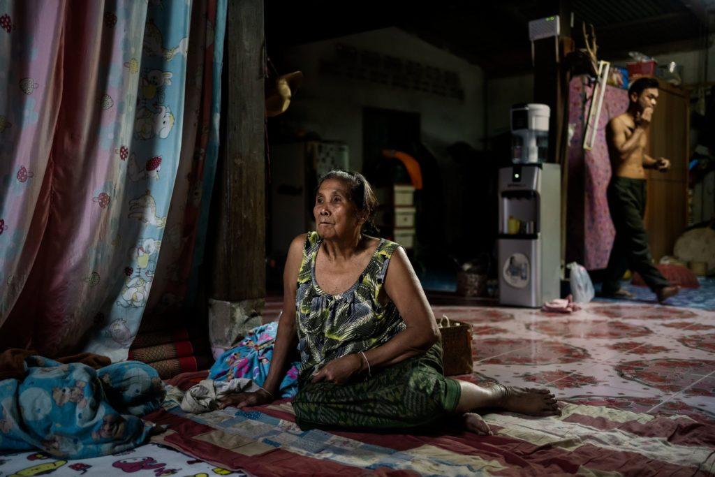 Bà Amkha Janlong xem TV trong lúc con rể, Wittaya Thongnet, đi phía sau, trong ngôi nhà họ sống bên sông Mekong. Ảnh: The New York Times.