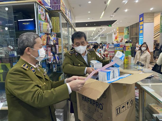 Lực lượng quản lý thị trường kiểm tra sản phẩm khẩu trang tại một hiệu thuốc. Ảnh: Người Lao Động.