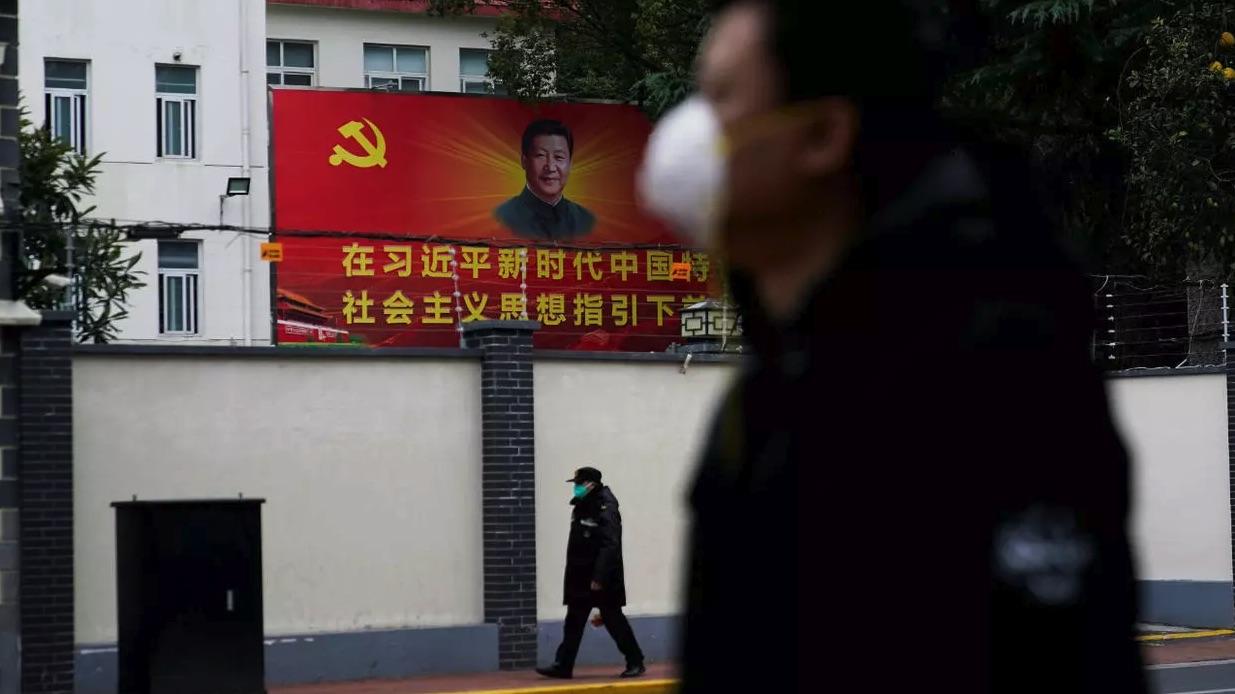 Người dân Trung Quốc đeo khẩu trang đi qua áp phích có chân dung Chủ tịch Tập Cận Bình, ngày 10/2/2020. Ảnh: Reuters.