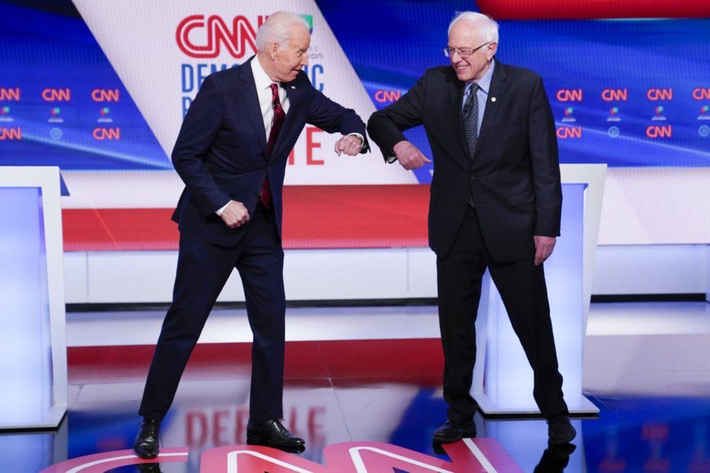 Hai ứng viên của Đảng Dân chủ, Joe Biden và Bernie Sanders đụng cùi chỏ tay thay vì bắt tay như thông lệ. Ảnh: CNN.