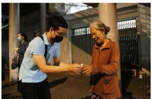 Một tình nguyện viên ở Sài Gòn tặng nước rửa tay cho một cụ già. Ảnh: plo.vn.
