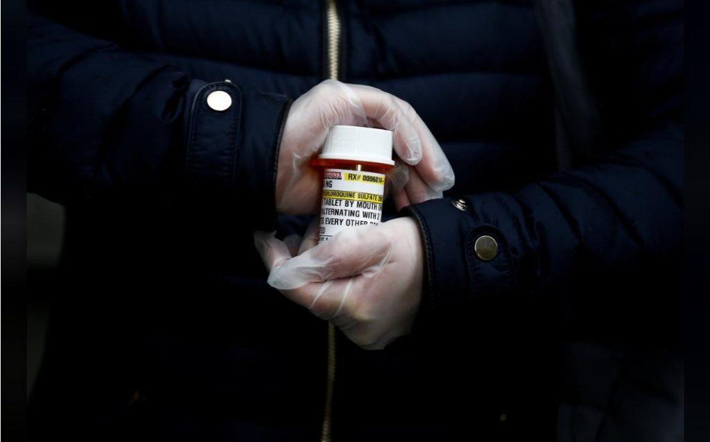 Một phụ nữ cầm lọ thuốc kí ninh ở bang Washington, Mỹ, ngày 31/3/2020. Ảnh: Reuters.