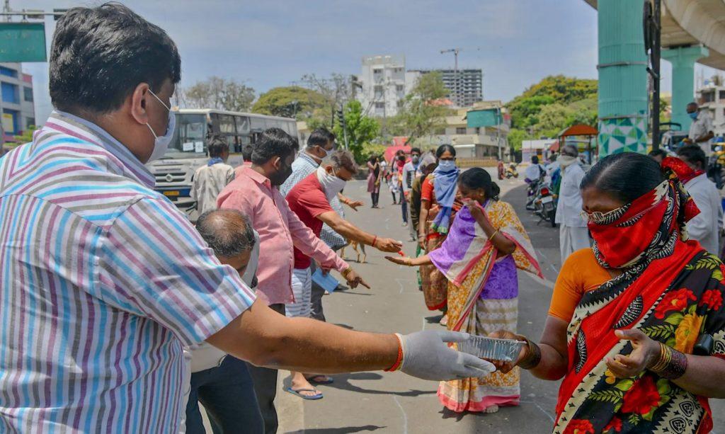 Người dân phân phát đồ ăn miễn phí ở Bangalore, Ấn Độ. Ảnh:  Manjunath Kiran/AFP via Getty Images.