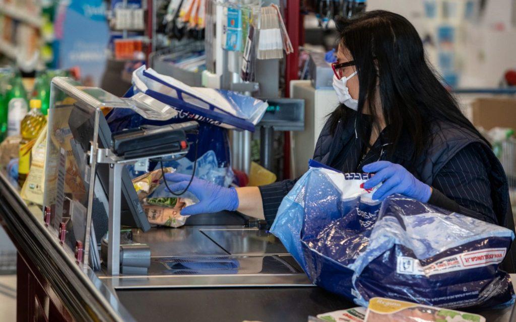 Một nhân viên đứng quầy ở một siêu thị ở Milan, Italy. Ảnh: Getty Images.