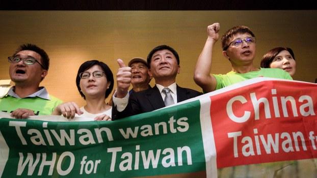 Bộ trưởng Y tế Đài Loan Chen Shih-chung (áo đen, giữa) trong một cuộc biểu tình kêu gọi WHO cho phép Đài Loan tham dự hội nghị ở Geneva, Thụy Sĩ, ngày 21/5/2018. Ảnh: AFP.