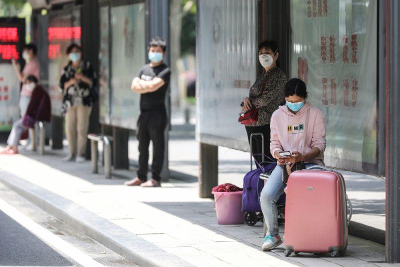 Hành khách tại một trạm xe bus ở Vũ Hán, Trung Quốc, ngày 11/5/2020. Ảnh: AFP.