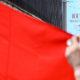 Một người ủng hộ Trung Quốc giương cờ Trung Quốc trước tấm biểu ngữ quảng cáo cho Luật An ninh Quốc gia tại Hong Kong, ngày 26/6/2020. Ảnh: Anthony WALLACE / AFP.