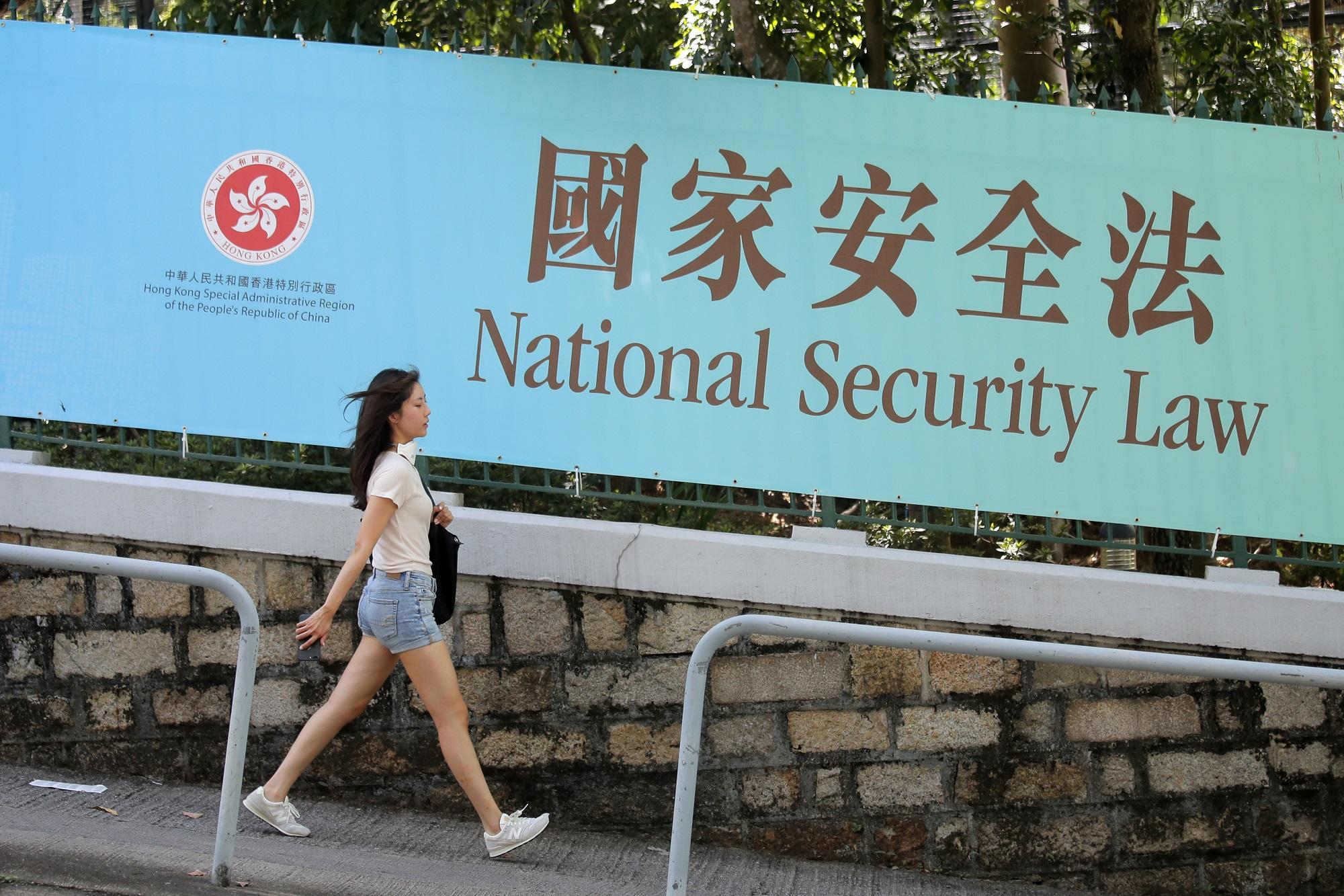 Một người đi bộ qua khu vực trưng biểu ngữ cổ động cho Luật An ninh Quốc gia ở Hong Kong, ngày 30/6/2020. Ảnh: AP.