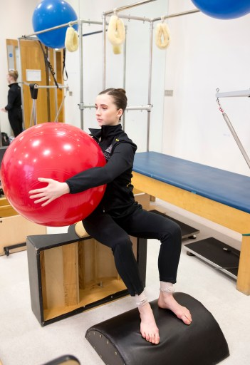 Royal ballet performer using an exercise ball as part of physiotherapy treatment.