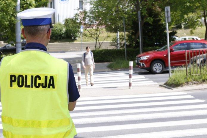Policjant ubrany w mundur patrzy na pieszą przechodzącą przez przejście.