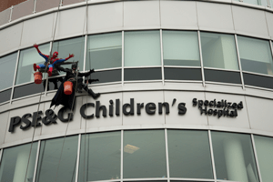 Window washers dressed as Batman and Spiderman rappel down the side of PSE&G Children's Hospital in New Brunswick, NJ
