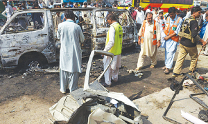 Source: DAWN: PESHAWAR: Security personnel and volunteers inspect the wreckage of the coach destroyed by the blast.—AFP