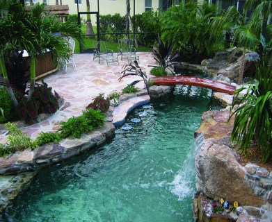 Lagoon Pool with Bar style seating, bridge, spa, flagstone deck and outdoor tiki kitchen