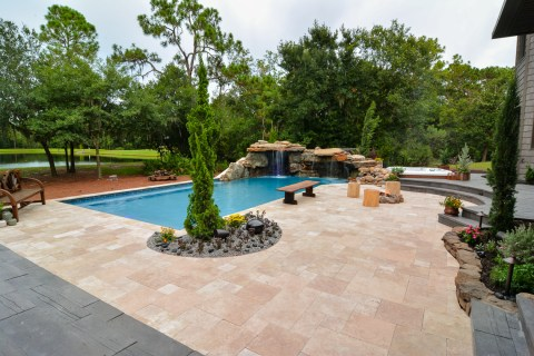 Looking out over the large travertine deck area of a great natural outdoor living space with a northern rock waterfall