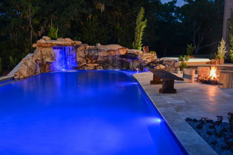 A natural lagoon pool glows with underwater and outdoor lighting along with the warm glow from a pool side fire pit.
