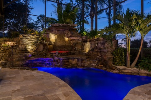 Spa under the waterfall with large travertine deck