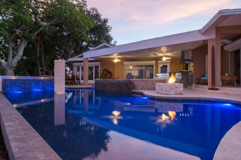 Looking back at the home and outdoor living area from the pool edge