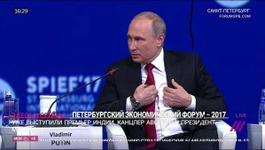 Putin speaking at Petersburg Economic Forum, seated