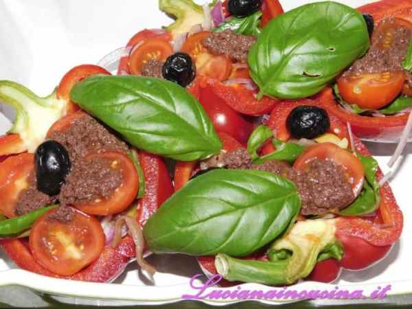 Riempire i mezzi peperoni con tutti gli ingredienti: il patè di olive, i filetti di alici, l'aglio, i pomodorini, le olive, le foglie di basilico spezzettate, le melanzane a tocchetti, le cipolle, terminando con un filo d'olio e regolando di sale e pepe.