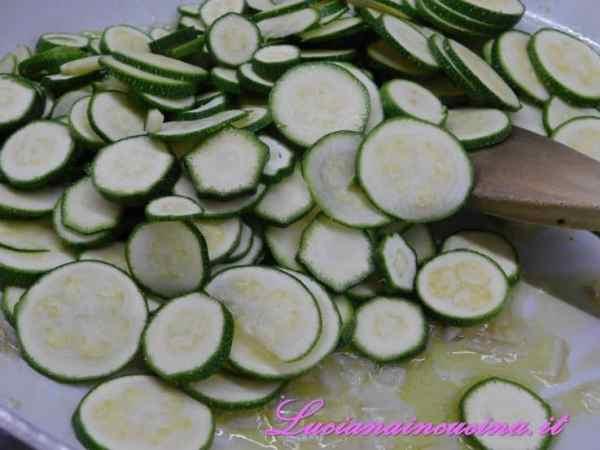 Dopo 2 minuti inserire le zucchine a rondelle, salare leggermente e cuocere per 5 minuti.